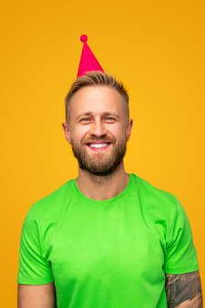 Vrolijke moderne getatoeëerde hipster in lichte t-shirt en feestmuts lachend
