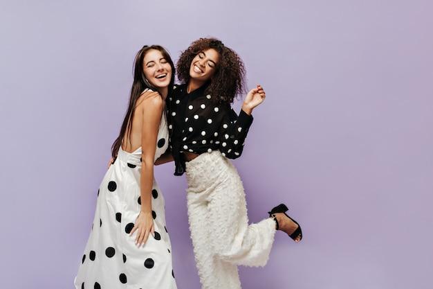 Vrolijke moderne vrouwen met donkerbruin kapsel in stijlvolle zomerkleren met stippen die glimlachen met gesloten ogen op geïsoleerde muur