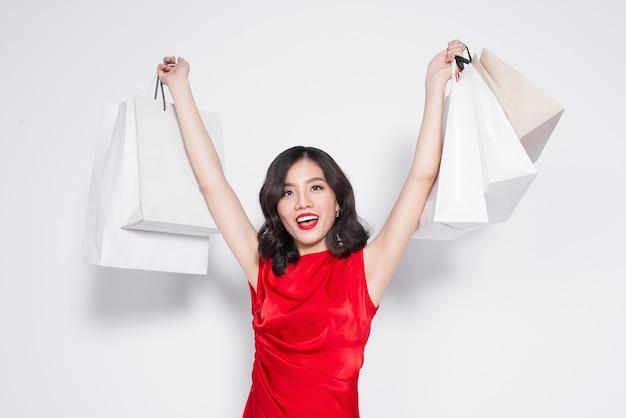 Vrolijke modieuze aziatische vrouw die een rode jurk draagt met boodschappentassen die over wit staan.