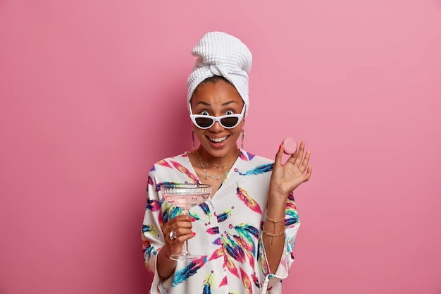 Vrolijke modieuze jonge dame gekleed in huiselijk gewaad en handdoek houdt macaron glas cocktail draagt trendy zonnebril geïsoleerd over roze muur. mensen stijl concept
