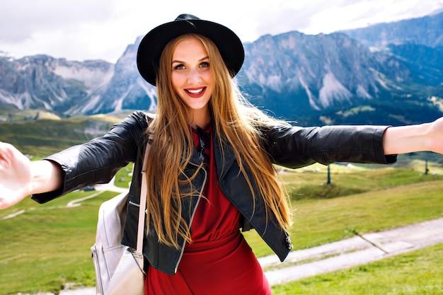 Vrolijke modieuze jonge modelvrouw die selfie bij alpbergen maakt, kleding, leerjasje, zonnebril en rugzak draagt