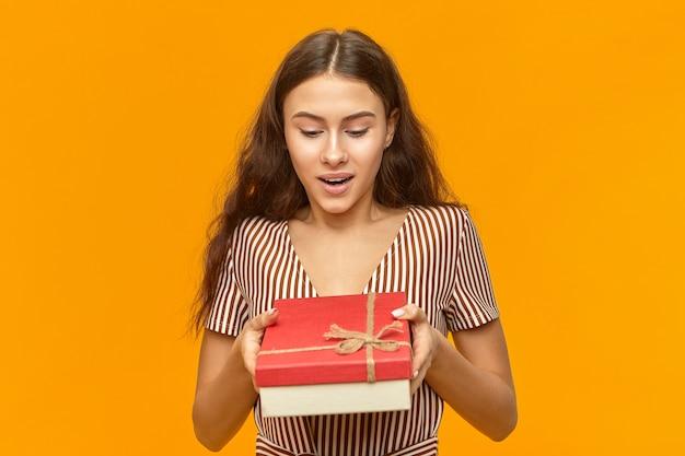 Vrolijke modieuze jonge vrouw die de mooie gestreepte doos van de kledingsholding draagt