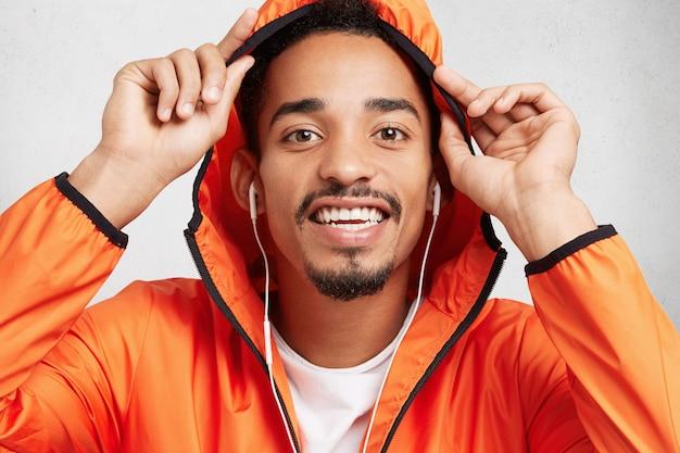 Vrolijke modieuze man glimlacht breed, toont witte, gelijkmatige tanden, draagt een capuchon van een anorak, luistert naar muziek in oortelefoons,