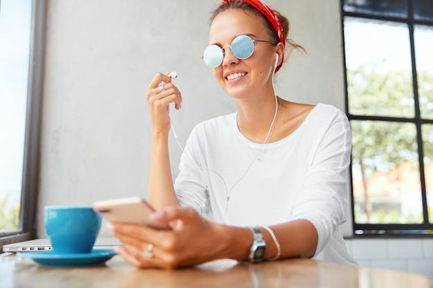 Vrolijke modieuze vrouw draagt een zonnebril, een witte trui en een rode hoofdband, luistert naar audio in haar eigen afspeellijst, geniet van vrije tijd in de coffeeshop. mooie vrouw vermaakt zichzelf met een elektronisch apparaat