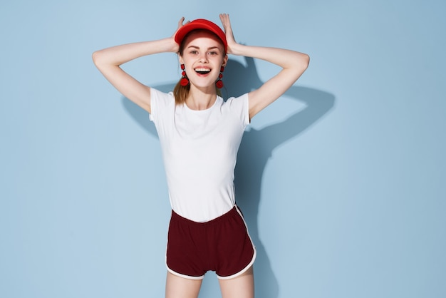 Vrolijke modieuze vrouw in zomer kleding studio glamour blauwe achtergrond