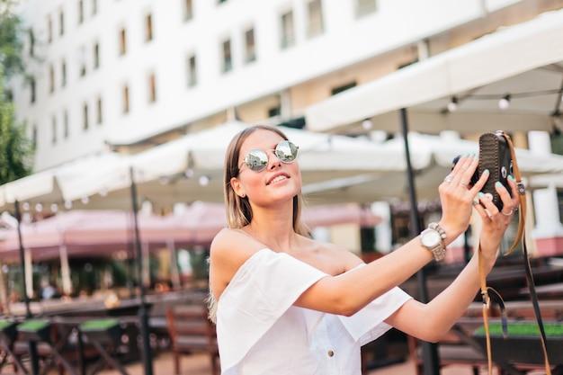 Vrolijke modieuze vrouw in zonnebril maakt foto's van zichzelf op retro camera in stedelijke omgeving