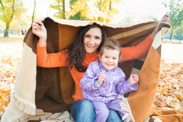 Vrolijke moeder, bedekt met een deken, met haar baby in het park