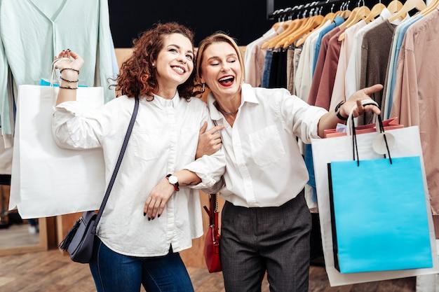 Vrolijke moeder. blondharige rijpe moeder voelt zich vrolijk en brengt tijd door met winkelen met haar meisje