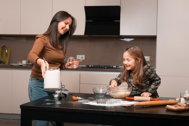 Vrolijke moeder die tijd met haar dochter heeft en wat koekjes in keuken voorbereidt