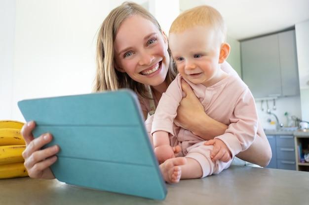Vrolijke moeder en baby praten met familie, tablet gebruiken voor videogesprek, samen glimlachen op scherm. kinderopvang of online communicatieconcept