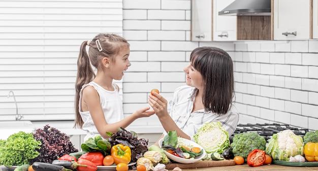 Vrolijke moeder en dochter bereiden een groentesalade van veel groenten op een lichte, moderne keuken.