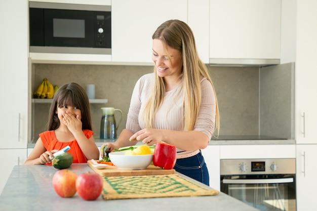 Vrolijke moeder en dochter chatten en lachen tijdens het koken van groenten voor het avondeten. meisje en haar moeder die groenten voor salade op aanrecht pellen en snijden. familie koken concept