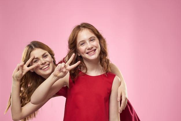 Vrolijke moeder en dochter die rode jurken dragen staan naast vreugdefamilie op roze achtergrond