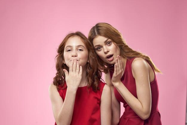 Vrolijke moeder en dochter die rode jurken dragen staan naast vreugdefamilie op roze muur.
