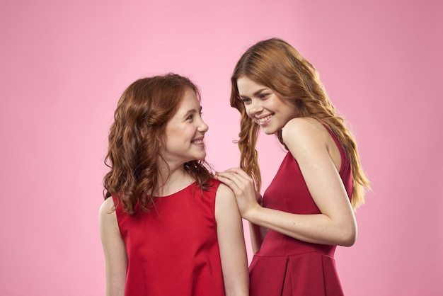 Vrolijke moeder en dochter die rode jurken dragen staan naast vreugdefamilie op roze