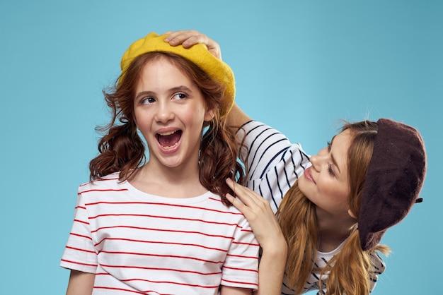 Vrolijke moeder en dochter dragen gestripte t-shirts op blauwe achtergrond