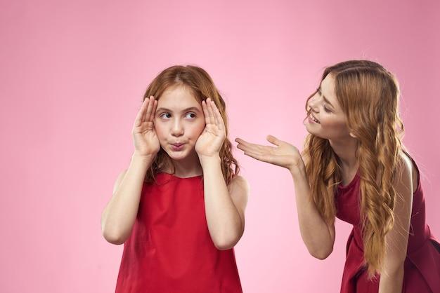 Vrolijke moeder en dochter dragen rode jurken op roze achtergrond