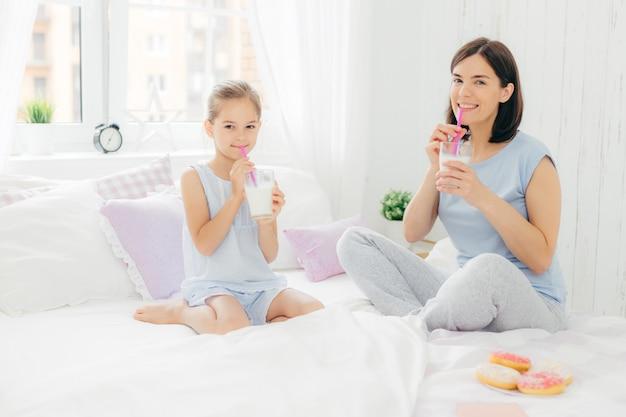 Vrolijke moeder en dochter gekleed in pyjama, ontbijten in de ochtend