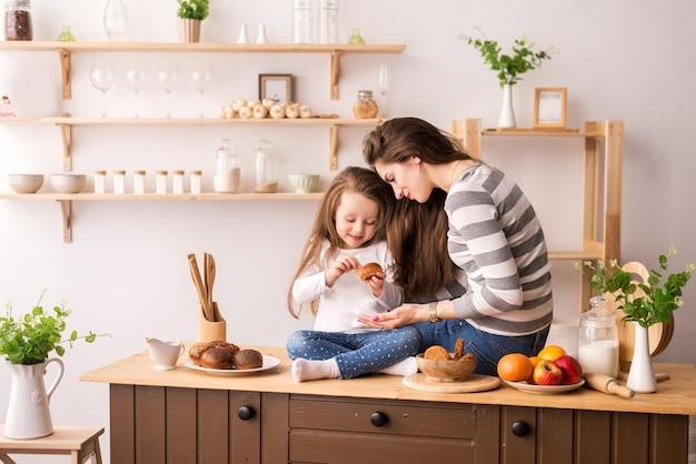 Vrolijke moeder en dochter in de keuken die ontbijt voorbereidt. ze eten koekjes, spelen pannenkoeken en lachen.