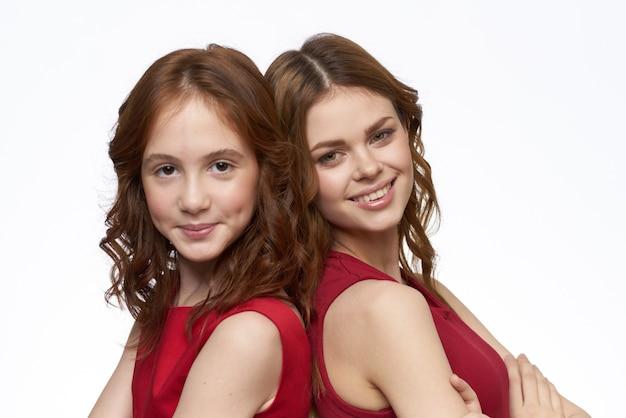 Vrolijke moeder en dochter in rode jurken socialiseren lichte achtergrond. hoge kwaliteit foto