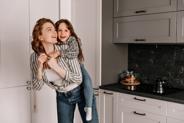 Vrolijke moeder en dochter in soortgelijke outfits spelen in de keuken en lachen.