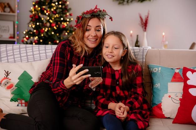 Vrolijke moeder en dochter kijken naar telefoon zittend op de bank en genieten van kersttijd thuis