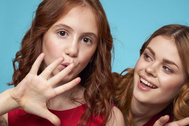 Vrolijke moeder en dochter knuffelen vreugde levensstijl communicatie vriendschap blauw