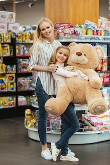 Vrolijke moeder en dochter met speelgoed