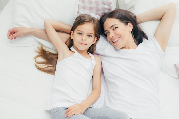 Vrolijke moeder en dochter omhelzen als liggen op witte beddengoed, wakker worden in de ochtend
