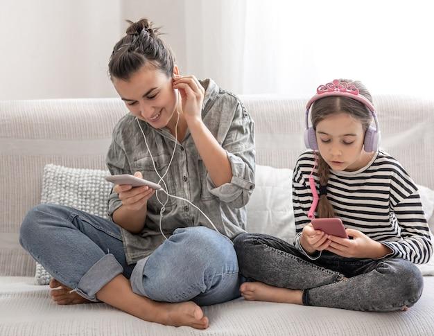 Vrolijke moeder en dochter rusten thuis, luisteren naar muziek op de koptelefoon