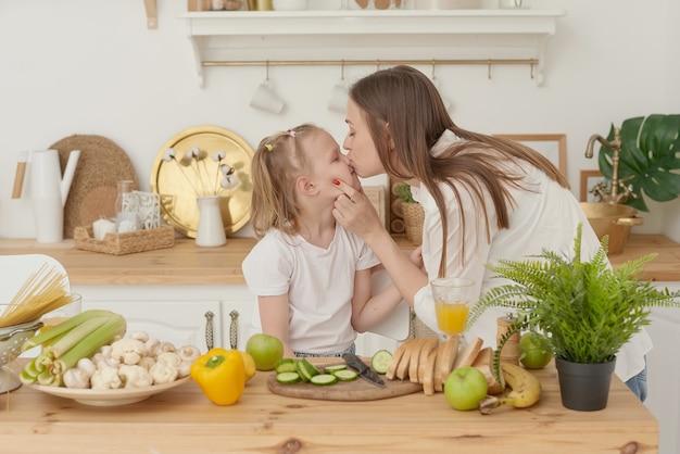 Vrolijke moeder en dochtertje bereiden samen salade in de keuken en hebben plezier. het meisje kust haar moeder thuis.