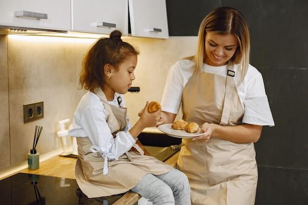 Vrolijke moeder en dochtertje die versgebakken koekjes eten in de keuken, genieten van zelfgemaakt gebak, schorten dragen en naar elkaar glimlachen, thuis plezier hebben.