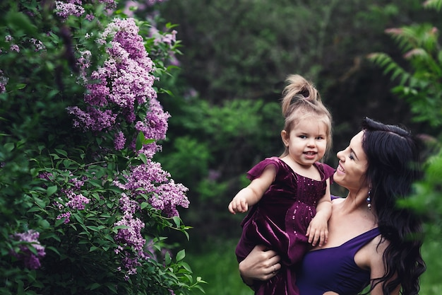 Vrolijke moeder en dochtertje in paarse jurken spelen in de natuur