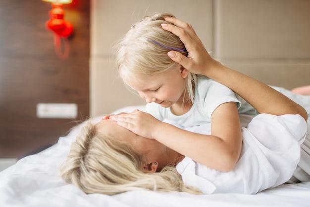 Vrolijke moeder en kind spelen thuis liggend op bed verstoppertje. oudergevoel, saamhorigheid, moederschap