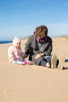 Vrolijke moeder en lieve kleine baby die warme kleren dragen, vrije tijd op zee doorbrengen, samen op zand zitten