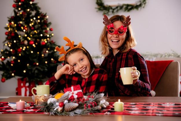 Vrolijke moeder in rendierglazen en dochter aan tafel zitten en genieten van de kersttijd thuis