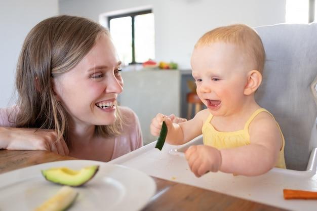 Vrolijke moeder kijken naar baby vast voedsel eten in hoge stoel, lachen en plezier maken. close-up shot. kinderopvang of voeding concept
