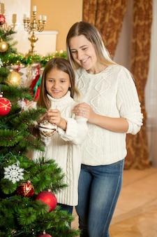 Vrolijke moeder met dochter kerstboom versieren met kleurrijke kerstballen