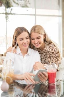 Vrolijke moeder met smartphone selfie maken met haar aanhankelijke dochter terwijl beide tijd doorbrengen in café na het winkelen