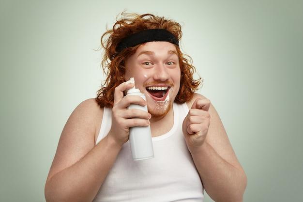 Vrolijke mollige jonge europese man met krullend gemberhaar die binnenshuis plezier heeft, spuitbus vasthoudt, zijn gezicht vuil met witte slagroom, kijkend met opgewonden en opgewonden gezichtsuitdrukking