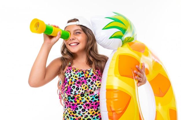 Vrolijke mooi meisje in een zwembroek en een baseballcap met een opblaasbare cirkel kijkt door een verrekijker op een wit
