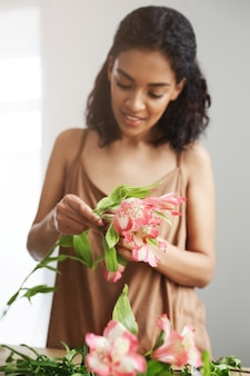 Vrolijke mooie afrikaanse bloemist die makend boeket op werkplaats over witte muur glimlachen.