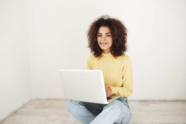 Vrolijke mooie afrikaanse vrouw die lacht zittend met laptop op verdieping.