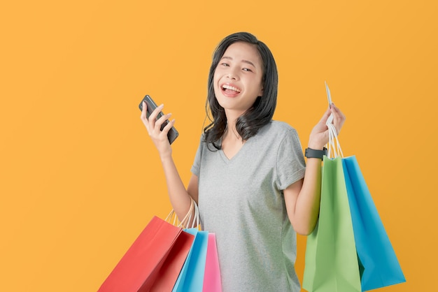 Vrolijke mooie aziatische vrouw die multi gekleurde het winkelen zakken en creditcard met smartphone op lichtoranje houden.