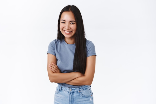 Vrolijke, mooie aziatische vrouw in t-shirt, spijkerbroek lachend en enthousiast over witte muur staan, handen over borst gekruist bescheiden grijnzend, rondhangen met nieuwe collega's tijdens feest