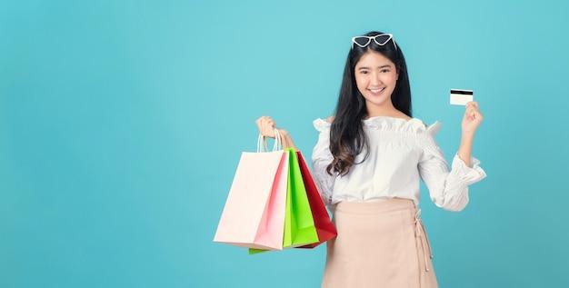 Vrolijke mooie aziatische vrouw met multi gekleurde boodschappentassen en creditcard op lichtblauw.