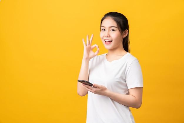 Vrolijke mooie aziatische vrouw met smartphone en ok teken vertoont
