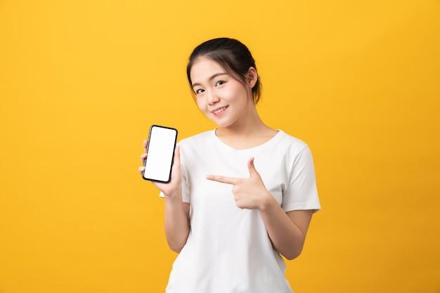 Vrolijke mooie aziatische vrouw met smartphone op lichtgele achtergrond.