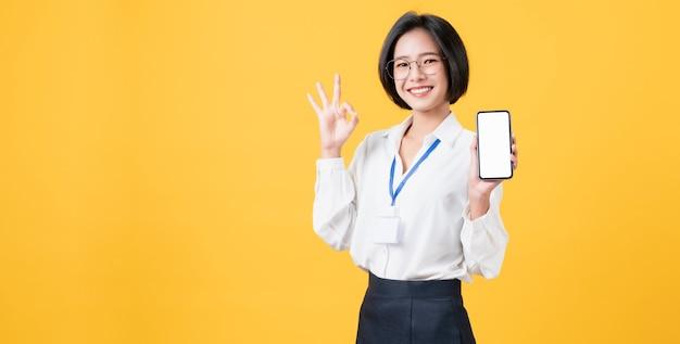 Vrolijke mooie aziatische vrouw met smartphone op lichtgele muur.