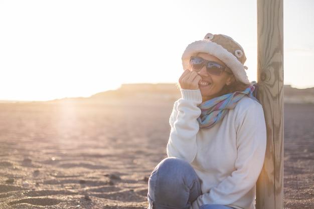 Vrolijke mooie blanke dame van middelbare leeftijd glimlachend en kijkend naar de camera met gouden zonsondergang op de achtergrond zittend op het strand in vrijetijdsbesteding in de buitenlucht of onafhankelijke vakantie